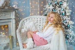 Recht blondes kleines Mädchen sitzt und träumt auf einem Stuhl nahe einem Kamin und einem Weihnachtsbaum Stockfotografie