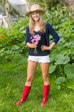 Recht blondes Lächeln an der Kamera, die Blumen hält Lizenzfreie Stockfotos