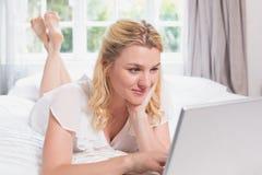 Recht blondes Lügen auf Bett unter Verwendung des Laptops Lizenzfreies Stockbild