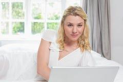 Recht blondes Lügen auf Bett unter Verwendung des Laptops, der an der Kamera lächelt Stockfotos