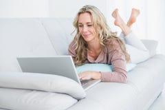 Recht blondes Lügen auf Couch unter Verwendung des Laptops Lizenzfreie Stockbilder