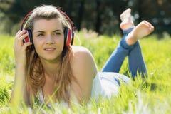 Recht blondes Lügen auf dem Gras, das Musik hört Lizenzfreie Stockfotografie