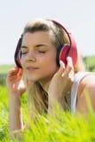 Recht blondes Lügen auf dem Gras, das Musik hört Lizenzfreies Stockfoto