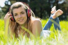 Recht blondes Lügen auf dem Gras, das Musik hört Stockfotografie