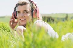 Recht blondes Lügen auf dem Gras, das Musik hört Lizenzfreies Stockbild
