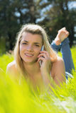 Recht blondes Lügen auf dem Gras, das am Telefon lächelt an der Kamera spricht Stockfotografie
