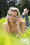 Recht blondes Lügen auf dem Gras, das am Telefon spricht Lizenzfreie Stockfotos