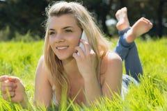 Recht blondes Lügen auf dem Gras, das am Telefon spricht Stockfoto