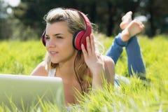 Recht blondes Lügen auf dem Gras unter Verwendung des Laptops hörend Musik Lizenzfreies Stockfoto