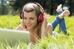 Recht blondes Lügen auf dem Gras unter Verwendung des Laptops hörend Musik Lizenzfreie Stockfotos