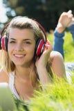 Recht blondes Lügen auf dem Gras unter Verwendung des Laptops hörend Musik Lizenzfreie Stockbilder