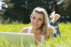 Recht blondes Lügen auf dem Gras unter Verwendung des Laptops lächelnd an der Kamera Stockfotos