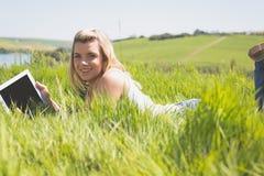 Recht blondes Lügen auf dem Gras unter Verwendung ihrer Tablette lächelnd an der Kamera Lizenzfreies Stockbild