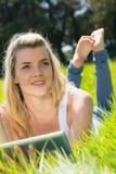 Recht blondes Lügen auf dem Gras unter Verwendung ihrer Tablette lächelnd an der Kamera Lizenzfreies Stockfoto