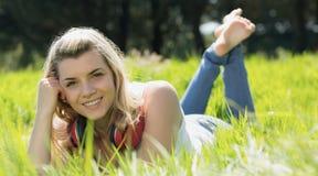 Recht blondes Lügen auf Gras mit Kopfhörern um Hals Stockfotografie