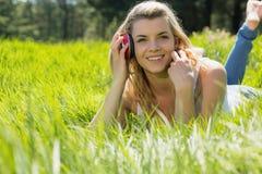 Recht blondes Lügen auf Gras mit Kopfhörern um Hals Lizenzfreie Stockfotos