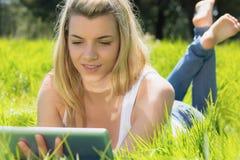 Recht blondes Lügen auf Gras unter Verwendung ihrer Tablette Lizenzfreie Stockfotografie