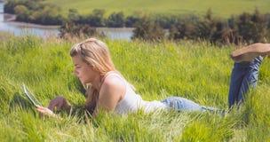 Recht blondes Lügen auf Gras unter Verwendung ihrer Tablette Stockbild