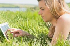 Recht blondes Lügen auf Gras unter Verwendung ihrer Tablette Lizenzfreie Stockfotos
