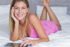 Recht blondes Lügen auf ihrem Bett unter Verwendung des Tabletten-PC, der an der Kamera lächelt Lizenzfreie Stockfotografie
