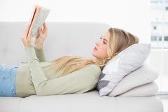 Recht blondes Lesebuch, das auf angenehmem Sofa liegt Lizenzfreie Stockfotos