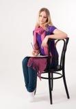Recht blondes Mädchen auf Stuhl Stockfoto