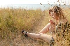 Recht blondes Mädchen, das auf Feld mit trockenem Gras sich entspannt Lizenzfreie Stockfotos