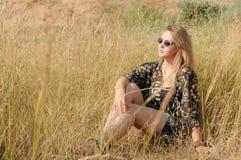 Recht blondes Mädchen, das auf Feld mit trockenem Gras sich entspannt Lizenzfreies Stockfoto