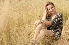 Recht blondes Mädchen, das auf Feld mit trockenem Gras sich entspannt Stockfotos