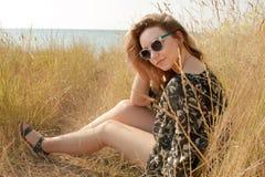Recht blondes Mädchen, das auf Feld mit trockenem Gras sich entspannt Stockbilder