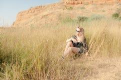 Recht blondes Mädchen, das auf Feld mit trockenem Gras sich entspannt Stockfoto