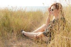 Recht blondes Mädchen, das auf Feld mit trockenem Gras sich entspannt Stockbild
