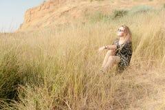 Recht blondes Mädchen, das auf Feld mit trockenem Gras sich entspannt Lizenzfreie Stockbilder