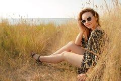 Recht blondes Mädchen, das auf Feld mit trockenem Gras sich entspannt Lizenzfreies Stockbild