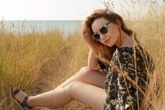 Recht blondes Mädchen, das auf Feld mit trockenem Gras sich entspannt Stockfotografie