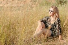 Recht blondes Mädchen, das auf Feld mit trockenem Gras sitzt Lizenzfreie Stockfotografie