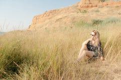 Recht blondes Mädchen, das auf Feld mit trockenem Gras sitzt Stockfotografie