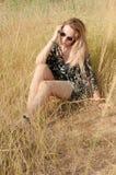 Recht blondes Mädchen, das auf Feld mit trockenem Gras sitzt Stockbilder