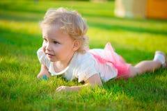 Recht blondes Mädchen, das auf Gras liegt Stockfoto