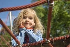 Recht blondes Mädchen, das auf Seil des roten Netzes im Sommer spielt Lizenzfreie Stockbilder
