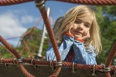 Recht blondes Mädchen, das auf Seil des roten Netzes im Sommer spielt Lizenzfreie Stockfotografie