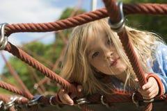 Recht blondes Mädchen, das auf Seil des roten Netzes im Sommer spielt Lizenzfreies Stockbild