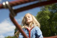 Recht blondes Mädchen, das auf Seil des roten Netzes im Sommer spielt Stockbild