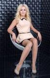 Recht blondes Mädchen, das auf weißem Stuhl sitzt Stockbilder