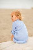 Recht blondes Mädchen, das das Meer übersehend sitzt Stockfoto