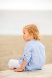 Recht blondes Mädchen, das das Meer übersehend sitzt Stockfotos