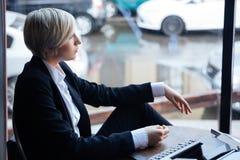 Recht blondes Mädchen, das an etwas im Café denkt Lizenzfreies Stockbild