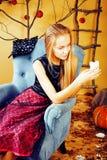 Recht blondes Mädchen, das Halloween im feenhaften Innenraum, glückliches lächelndes Leutekonzept des Lebensstils selebrating ist Stockfotos