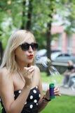 Recht blondes Mädchen in den Sonnenbrilleschlagblasen Stockbild