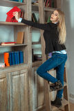 Recht blondes Mädchen in der Bibliothek nahe bei den Büchern Lizenzfreie Stockfotos